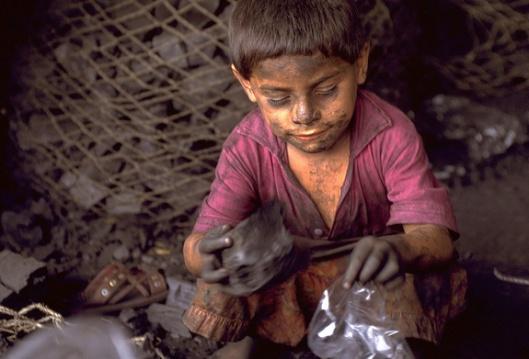Foto: UNICEF/Donna DeCesare Tonio Jorge, 6 år, i El Salvador fyller små plastpåsar med kol som hans familj säljer på marknaden där de bor.